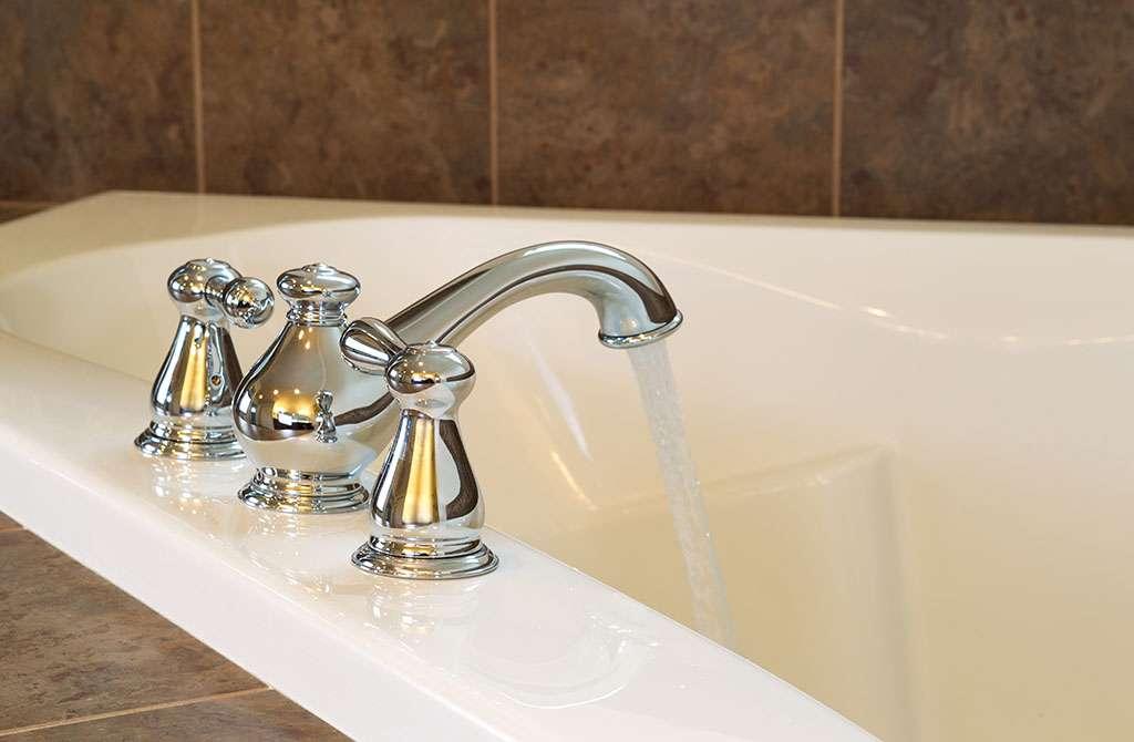 Closeup horizontal photo of chrome faucet running water into soaking tub in master bathroom